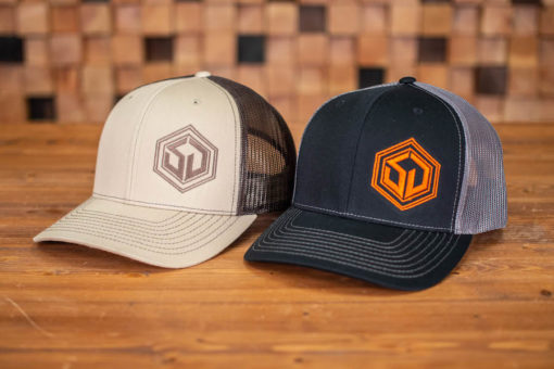 both survival dispatch trucker hats on a wood plank table