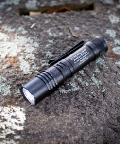 streamlight black flashlight on a rock with moss